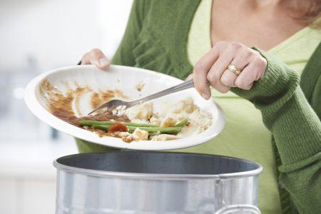 Woman Scraping Food Leftovers Into Garbage Bin